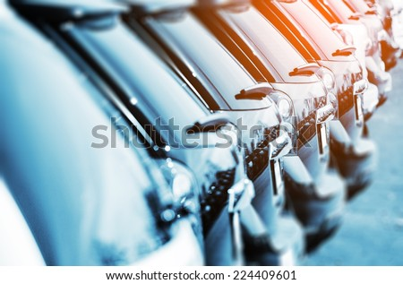 New Vehicles in Stock Closeup Photo with Color Grading. Brand New Cars For Sale in a Row. Cars Industry. - stock photo