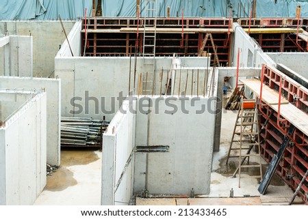 New walls being erected on a construction site with steel enforcements and scaffolding - stock photo