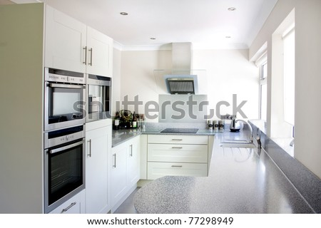 new white modern kitchen and stainless steel appliances - stock photo