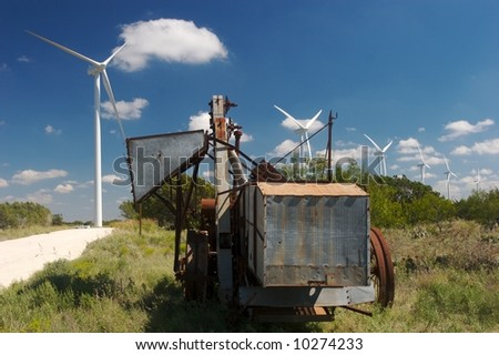 new Wind farm with old rustic farm equipment - stock photo