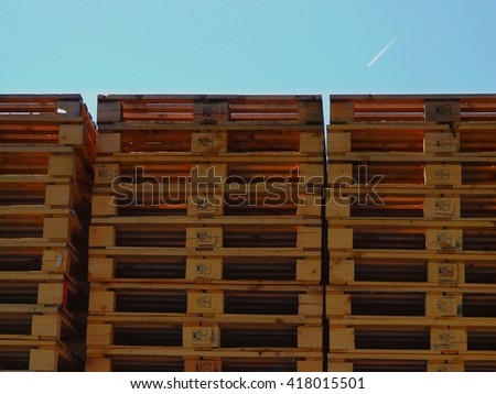New wooden euro pallets stocked outside at transportation company, stored pallets - stock photo