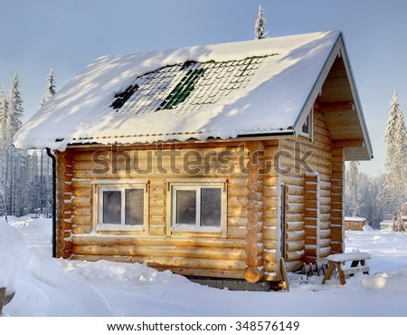 New wooden Russian bathhouse in a snowy winter forest, sunny day. - stock photo