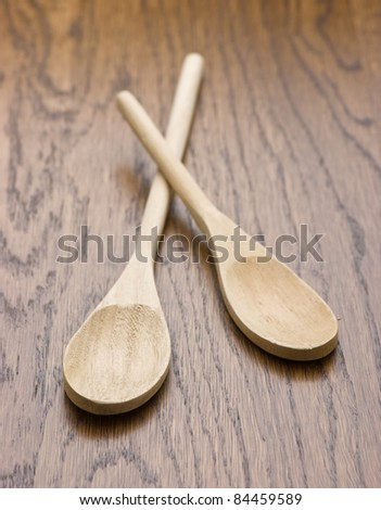 New wooden spoon on wooden table - stock photo