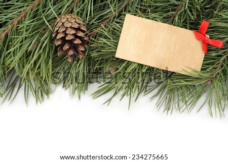New Year background. Christmas fir branches, bumps and wooden plate decorated with a bow on a white background. - stock photo
