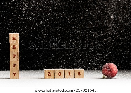 New Year 2015 background with falling snow and a red Christmas bauble with the word Happy spelled out on stacked wooden blocks with the date 2015 alongside over black with copyspace for your greeting. - stock photo