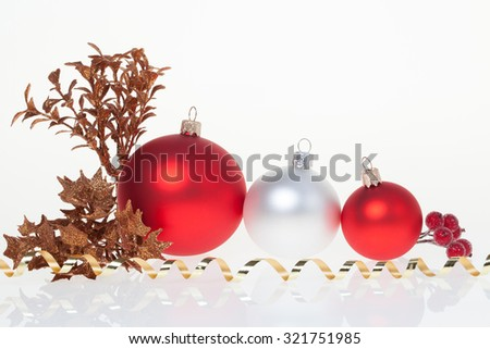 New Year background with three golden glass New Year toys and branch of rowan and decorative leafs - stock photo