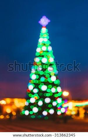 New Year Boke Lights Xmas Christmas Tree And Festive Illumination. Defocused Blue Bokeh Background Effect. Design Backdrop. - stock photo