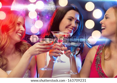 new year, celebration, friends, bachelorette party, birthday concept - three women in evening dresses with cocktails and disco ball - stock photo