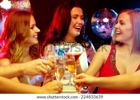 new year celebration, friends, bachelorette party, birthday concept - three women in evening dresses with cocktails in club or bar