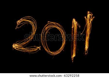 New Year celebration sparklers writing 2011 against black background. - stock photo