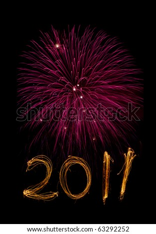 New Year celebration sparklers writing 2011 below pink fireworks against black background. - stock photo