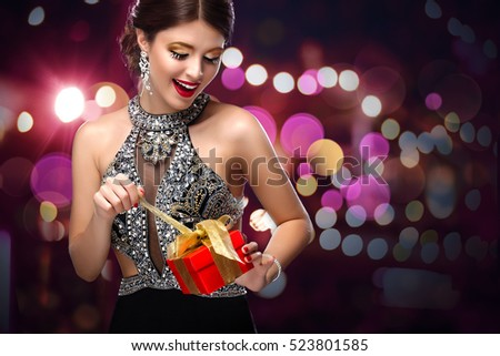 New Year, christmas, valentines day, birthday, people and holidays concept - smiling woman in dress with gift box over lights background. 2017