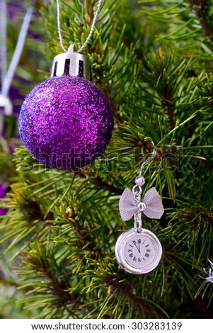 new year clock before midnight on the tree with a Christmas toy - stock photo