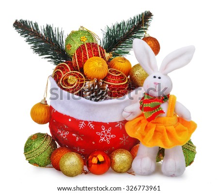 New year composition with santa claus bag, christmas baubles and white doll rabbit in yellow dress - stock photo