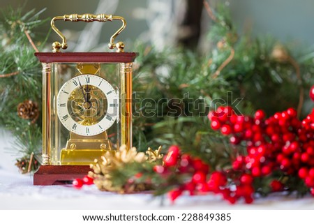New Year composition with the Carriage clocks, Christmas tree branches and red berries
