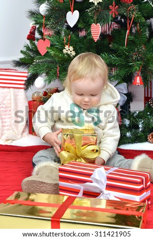 New year concept. Child baby toddler kid sitting under decorated christmas tree preparing presents gifts for celebration isolated on a white background - stock photo