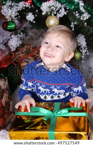 New Year concept. Happy little boy sitting under the Christmas tree with a great gift. Winter holidays