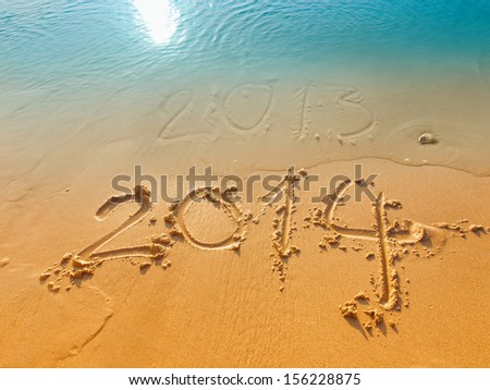 New Year 2014 concept-written in sand on the beach New Year's Eve 2013 and New Year 2014 on a beach sand  - stock photo