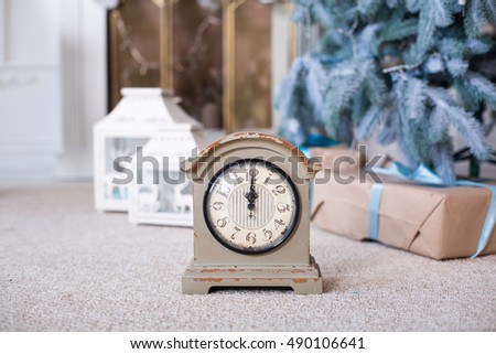 New Year decorations in blue and beige colors. Decorative white vintage clock, lanterns and gift boxes under fir-tree. Christmas mood