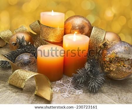 New Year festive still life with three burning candles, conifer branches, golden lace and baubles on yellow background with bokeh lights. Traditional New Year and Christmas celebratory decorations - stock photo
