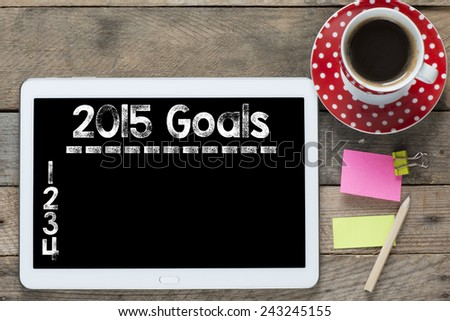 New year goals 2015. Tablet computer with stickers,cup of coffee and New year goals 2015 on the wooden table - stock photo