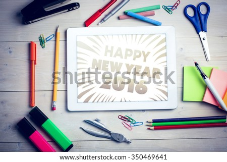 New year graphic against students desk with tablet pc