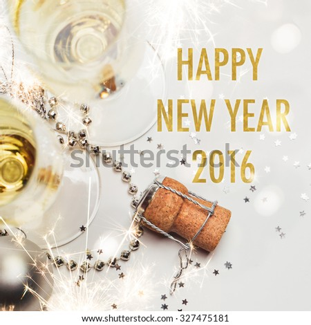 New year 2016 greeting card.Two champagne glasses and cork with baubles, sparklers, confetti and lights.  - stock photo