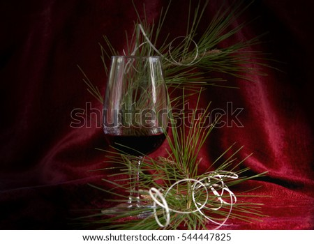 New Year greetings, glass of wine, pine branch with serpentine to the claret background Drapery