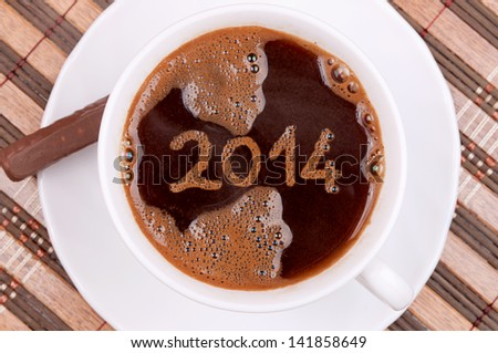New year 2014 handwritten on the coffee surface in the cup, with coffee foam texture - stock photo