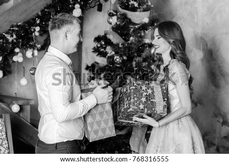 New year holiday portrait of a man and woman surprising him with a Christmas gift. Couple celebrating Christmas together. Beautiful young couple is celebrating at cozy romantic place.