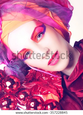 New Year Holiday. Young woman in pink and red turban and with artistic visage. - stock photo