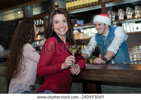 New Year in a bar. Young and beautiful girl is standing in a bar or pub and smiling. Bartender in Christmas hat is standing behind bar counter. Christmas is good with right cocktail
