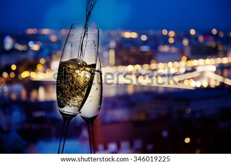 New year in the city - champagne glasses and city lights in the background - stock photo