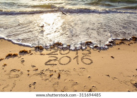 New Year 2016 is coming concept. 2015 and 2016 signs on a beach sand