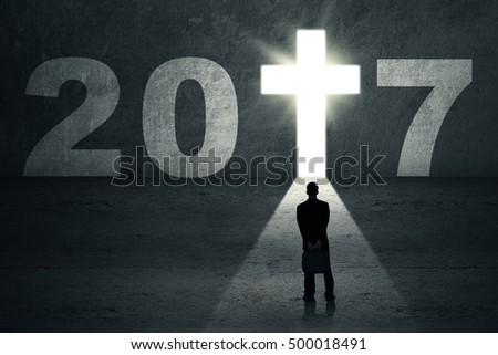 New Year 2017 is coming concept. Businessman standing in front of a doorway shaped a cross symbol with number 2017
