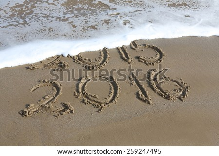 New Year 2016 is coming concept - inscription 2015 and 2016 on a beach sand, the wave is almost covering the digits 2015 - stock photo