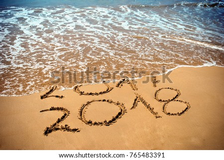 New Year 2018 is coming concept - inscription 2017 and 2018 on a beach sand, the wave is covering digits 2017. New Year 2018 celebration on New Year`s Eve tropical island travel tour.