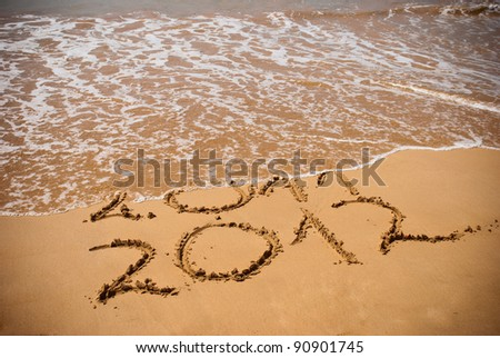 New Year 2012 is coming concept - inscription 2011 and 2012 on a beach sand, the wave is covering digits 2011 - stock photo