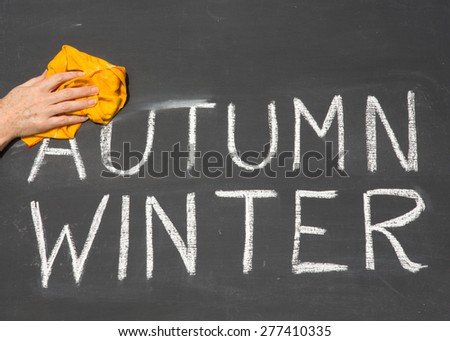 New Year is coming concept - inscription Autumn and Winter on a school blackboard, with the words Autumn being erased by the teacher. - stock photo