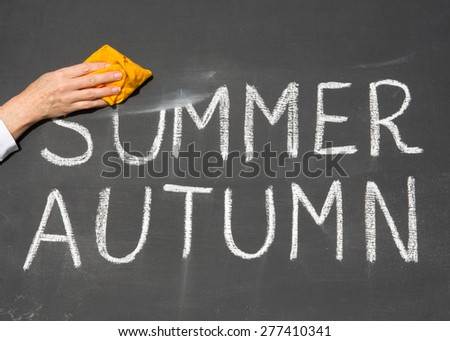 New Year is coming concept - inscription Summer and Autumn on a school blackboard, with the words Summer being erased by the teacher. - stock photo