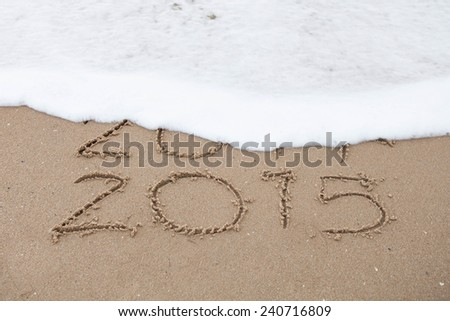New Year 2015 is coming concept on a beach sand, the wave is covering digits 2014 - stock photo