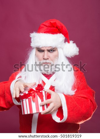 New year man with serious face with long white beard and hair in red santa claus christmas coat holding present box on purple background