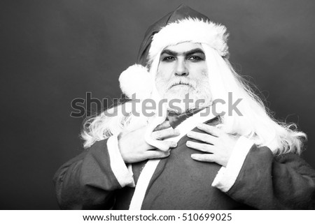 New year man with serious face with long white beard and hair in santa claus christmas coat on studio background, black and white