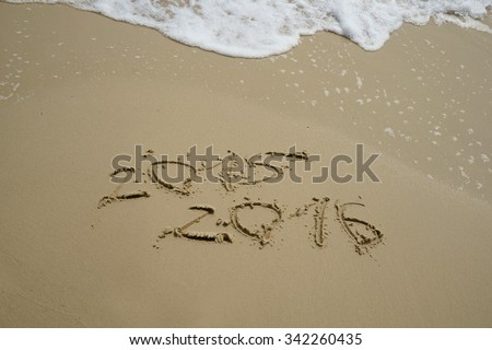 new year numbers 2015 and 2016  drawings in the sand on the beach - stock photo
