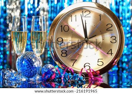 New year party decoration with champagne and clock close to midnight - stock photo