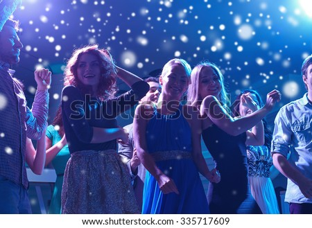 new year party, holidays, celebration, nightlife and people concept - group of happy friends dancing in night club and snow effect - stock photo