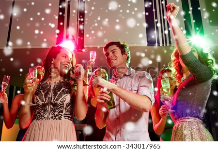 new year party, holidays, celebration, nightlife and people concept - smiling friends clinking glasses of non-alcoholic champagne and beer in club and snow effect - stock photo