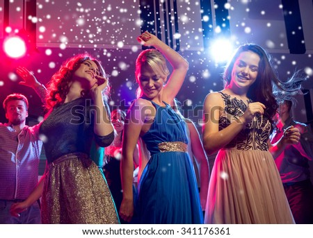 new year party, holidays, celebration, nightlife and people concept - smiling friends dancing in club and snow effect