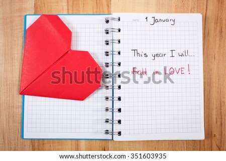 New year resolution fall in love written in notebook, red heart of paper, symbol of love - stock photo
