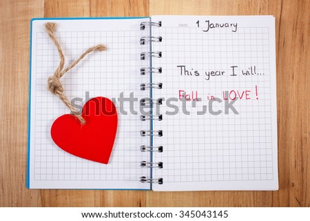 New year resolution fall in love written in notebook, red wooden heart, symbol of love - stock photo
